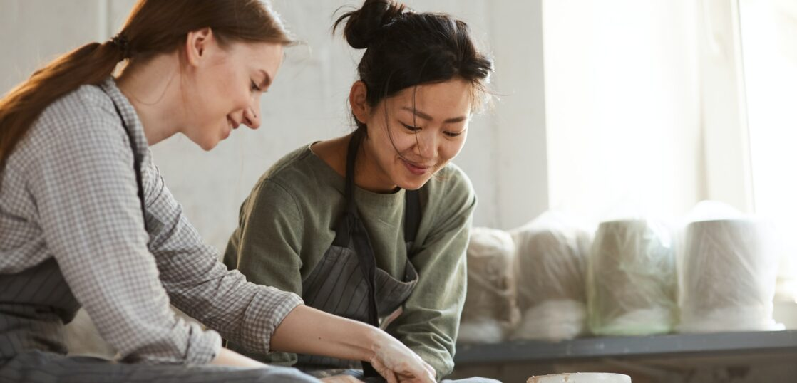 Content multi-ethnic women creating clay pot together